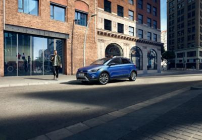 The new Hyundai i20 Active, pictured from the side, seen standing before a storefront.