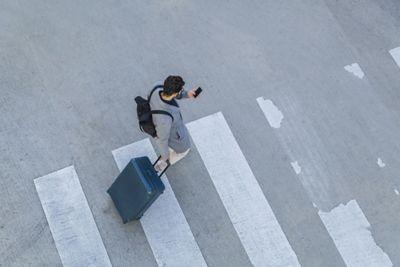 Hombre utilizando el sistema de navegación hasta destino en su smartphone mientras cruza la calle