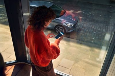 A young woman looking at her smartphone behind a large window with an all-new i20 parked outside