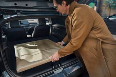 A man in a brown coat putting a wrapped painting into the all-new Hyundai i20's boot