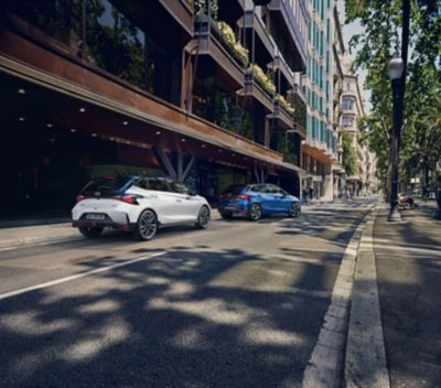 The Hyundai i20 N Line parked next to large buildings in an otherwise empty street