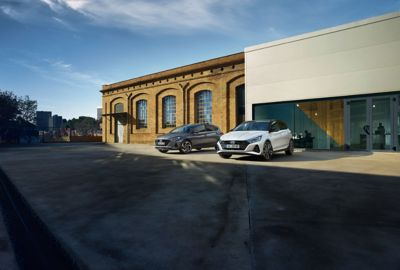 The Hyundai i20 N Line and i20 in aurora grey parked next to large building.