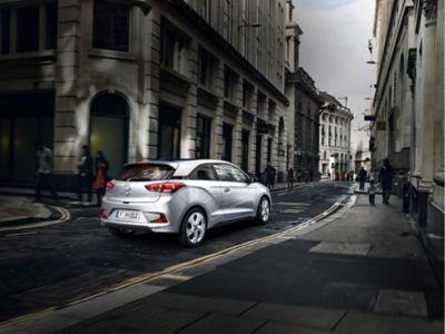 The Hyundai i20 Coupe, pictured from the rear and side as it drives on a street.