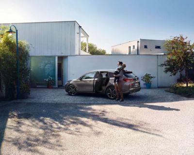 Muž s dítětem v náručí před svým vozem Hyundai i30 kombi.