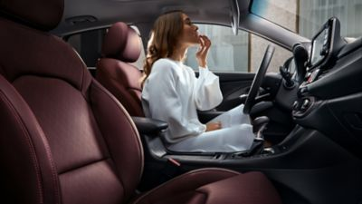 The Merlot interior of all-new Hyundai i30 Fastback pictured with a woman in the driver's seat.