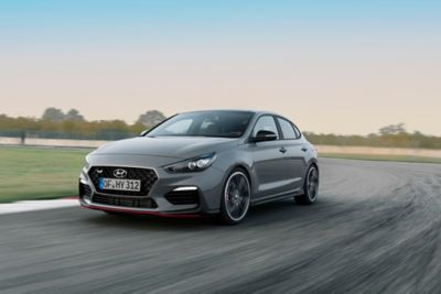 The Hyundai i30 Fastback N pictured driving on a race track.