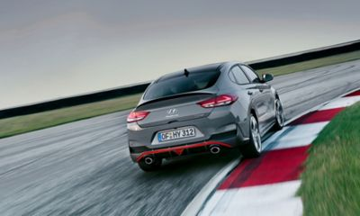 The Hyundai i30 Fastback N pictured from the rear taking a corner on a racetrack.