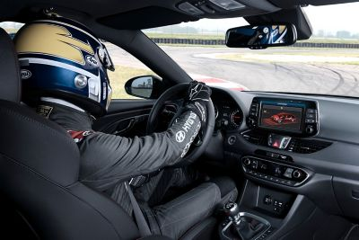 A race car driver pictured driving on a track in the Hyundai i30 Fastback N.