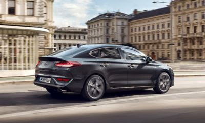 Picture of the new Hyundai i30 Fastback from the side driving on a city street.
