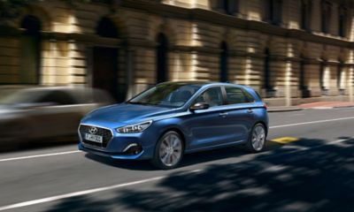 Photo of the new Hyundai i30 driving on a city street.
