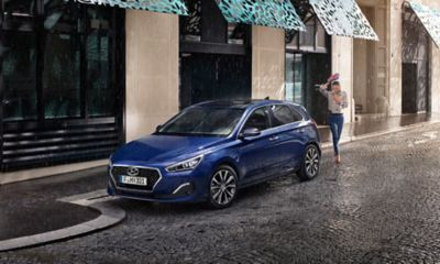 Picture of the new Hyundai i30 parked on a street in the rain.