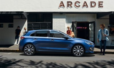 The new Hyundai i30 pictured from the side parked in front of a store front.