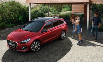 The i30 Wagon, pictured from above, standing in front of a family home.