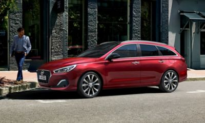Photo of the new Hyundai i30 Wagon, pictured from the side, standing on a sunlit street.