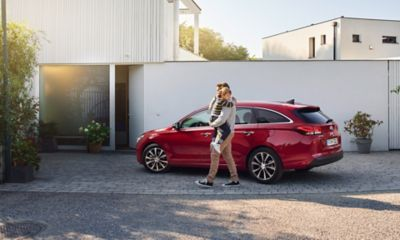 The new Hyundai i30 Wagon standing before a family home.