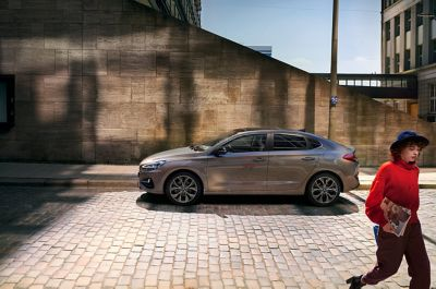 The all-new Hyundai i30 Fastback pictured from the side parked on a city street.