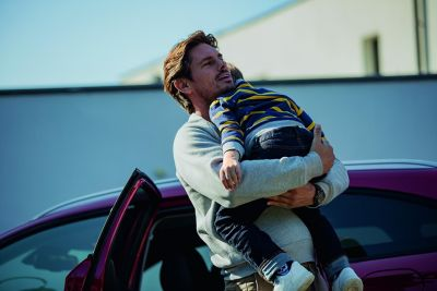Mężczyzna przed domem bierze na ręce dziecko i usadza go w samochodzie Hyundai.