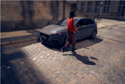 Kobieta w pomarańczowym swetrze przechodzi obok samochodu i30 Hatchback.