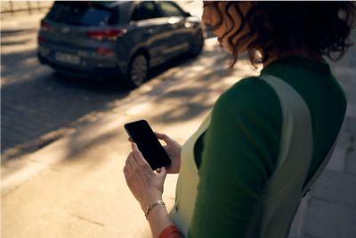 Kobieta ze smartfonem i nowym Hyundaiem i30 w tle.