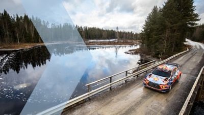 Hyundai Motorsport vehicle driving over a bridge across a lake