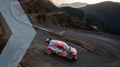 Hyundai i20 Coupe WRC driving down the hill approaching a hairpin bend