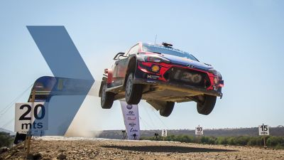 Hyundai i20 Coupe WRC lifting off the ground whilst being driven on a gravel road.