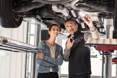 Ekspert serwisowy ASO Hyundai pokazuje kobiecie nadwozie.