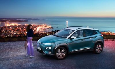 The all-new Hyundai Kona Electric standing before a city panorama.