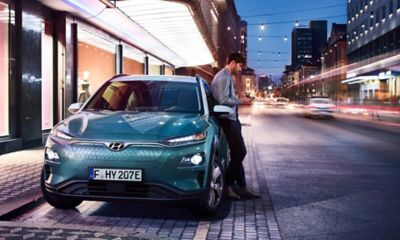 The all-new Hyundai Kona Electric, seen from the front on a city street at night.