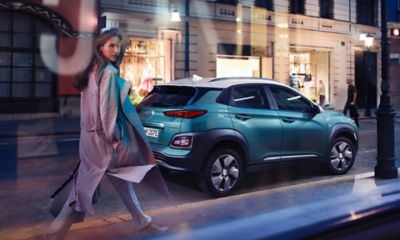 The all-new Hyundai Kona Electric, pictured from the side, standing on a city street.