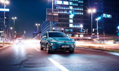 The all-new Hyundai Kona Electric seen driving on a street.