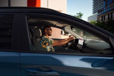 Un uomo alla guida di Nuova Hyundai Kona Electric.