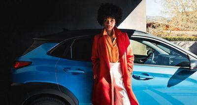 Una mujer con un abrigo rojo apoyada en la puerta de pasajero del Hyundai KONA Híbrido.