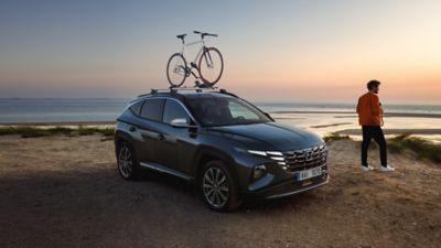 Hyundai Tucson na pláži, řidič kouká na západ slunce.