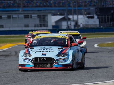 A picture of Hyundai Motorsport customer racing Veloster N TCR in action on a racetrack shown from the side