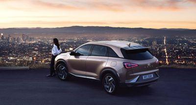 Vista del Hyundai NEXO frente a un edificio futurista al atardecer.