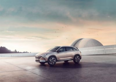The all-new Hyundai Nexo, shown from the side, standing before a futuristic building at sunset.