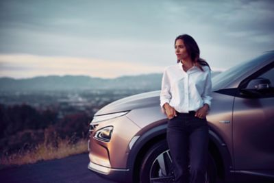 A woman standing before the all-new Hyundai Nexo before a city panorama.