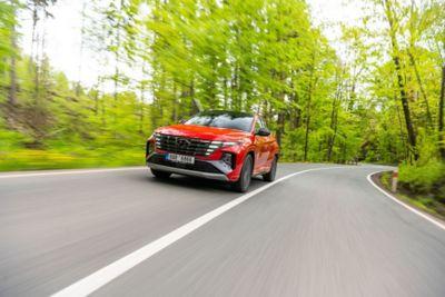 TUCSON N Line v červené barvě na silnici vedoucí lesem.