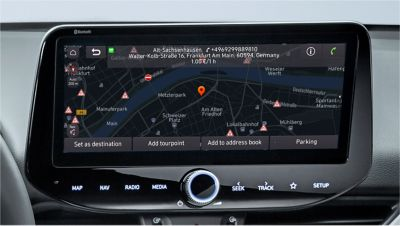 Close-up of a Hyundai touchscreen showing the location of a parking garage including cost per hour.
