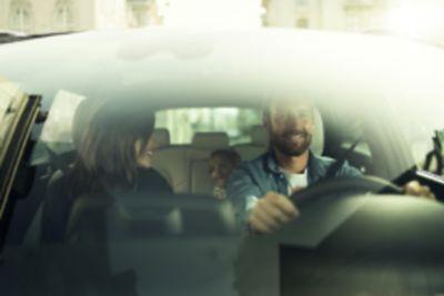 Vista a través de la luna delantera de una familia disfrutando dentro de un Hyundai.