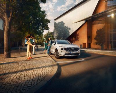 Nové 7místné SUV Hyundai Santa Fe v šedé barvě zaparkované před luxusním rodinným domem.