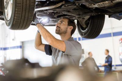 Ekspert z serwisu Hyundai sprawdza stan pojazdu pod podnośnikiem