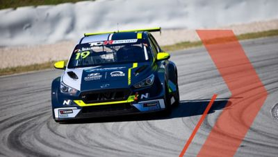A picture of Hyundai Motorsport's i30 VELOSTER N TCR in action on a racetrack shown from the front.