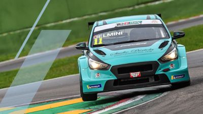 The Hyundai Motorsport's i30 N TCR in action on a racetrack in a corner.