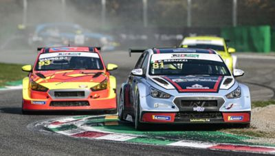 The Hyundai Motorsport customer racing i30 N VELOSTER carving corners in a race.
