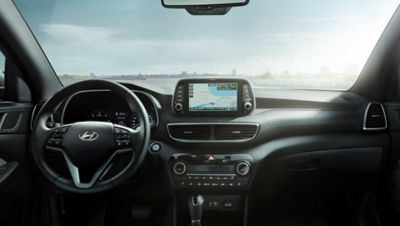 View of the new Hyundai Tucson's cockpit with steering wheel and screen visible.