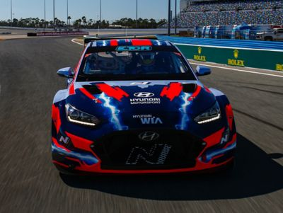 The Hyundai VELOSTER N ETCR from the front on a racetrack.