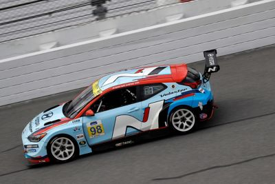 A picture of Hyundai Motorsport's i30 N TCR in action on a racetrack shown from the side.