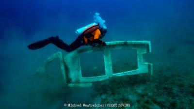 Een duiker van Ghost Divers ruimt afval op.